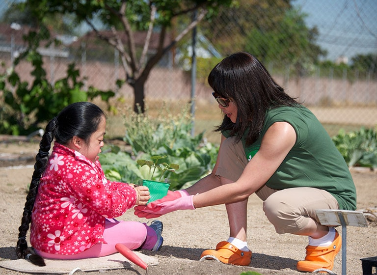 A female Mitsubishi Electric volunteer squats handing a plant to a girl with down syndrome in a garden.