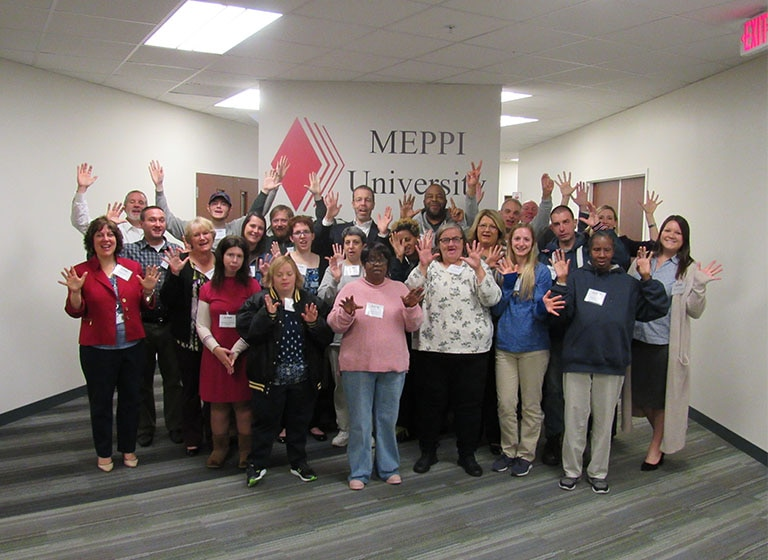 Twenty-three Mitsubishi Electric volunteers and clients from Life'sWork stand in front of a 'MEPPI University' sign.