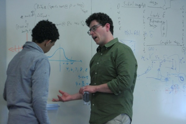 Standing in front of a whiteboard with equations, a male Mitsubishi Electric engineer mentors a young man.