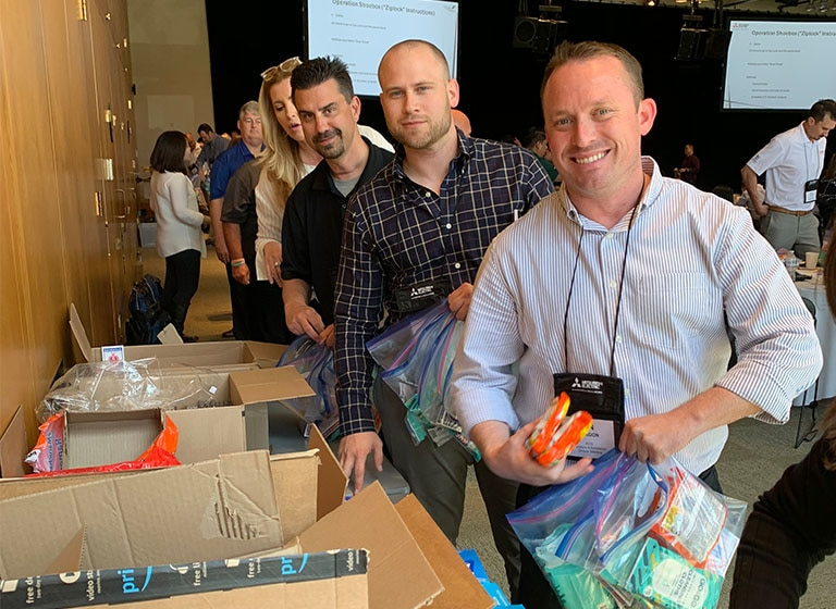 Smiling Mitsubishi Electric volunteers assemble care packages for Operation Shoebox.