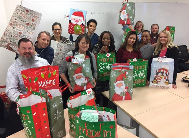 Eleven smiling Mitsubishi Electric volunteers hold holiday gift bags filled with presents.