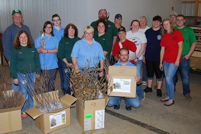 Seventeen Mitsubishi Electric volunteers pose hold boxes containing saplings in a barn.