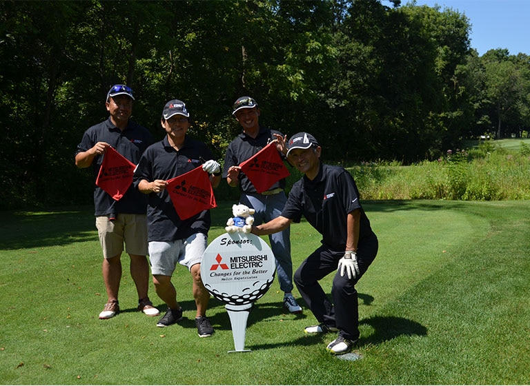 Four Japanese men in golf outfits stand in front of a hole marker that reads 'Mitsubishi Electric.'