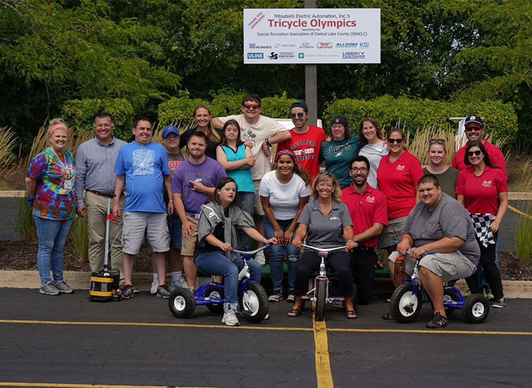 Twenty Mitsubishi Electric volunteers in a parking lot, 3 on large tricycles, pose in front of a 'Tricycle Olympics' sign